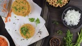 pois chiches : Raw veggie burger with chickpeas, vegetables and parsley leaves on kitchen countertop. Vidéos Libres De Droits
