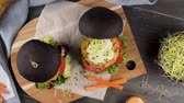 pois chiches : Tasty grilled veggie burgers with chickpeas and vegetables on black bread on dark wooden countertop. Vidéos Libres De Droits