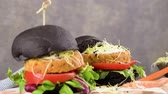empanadilla : Tasty grilled veggie burgers with chickpeas and vegetables on black bread on dark wooden countertop. Archivo de Video