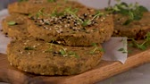 Raw veggie burger with lentils, dry tomato and thyme on wood cutting board. Stock Footage