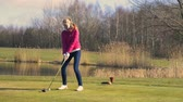 activities : Woman teeing off at a golf course