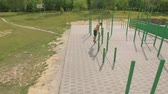 push ups : People train on an outdoor sports field in summer, aerial shot Stock Footage