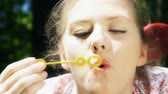 arrelia : Close up of a girl blowing bubbles lying down on the grass Stock Footage