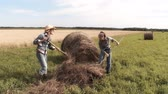video of two girl working on a farm and gathering hay Стоковые видеозаписи