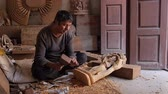 Sculptor artist carving wood in a Nepal work shop Стоковые видеозаписи