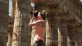 Woman taking pictures of an ancient Greek temple during vacation