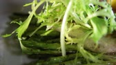 baars : Close-up of blanched asparagus and grilled fillet of pike perch, served with lemon and herbs on a white plate.Macro Stockvideo