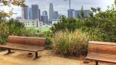 viagens de negócios : 4K UltraHD View of Los Angeles skyline with park bench in front