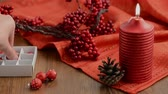 decorativo : putting Christmas decoration on a candle like Christmas balls, pearls, pine cone and red sock. Vídeos
