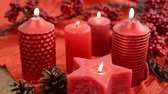 decorativo : four burning red candles with pine cone. Christmas decoration. in background twig with red berries. Vídeos