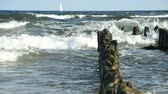 breaker : strong surf of the Baltic sea with sailboat
