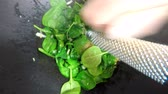 noz moscada : roasting fresh spinach in a chinese wok and adding the spice nutmeg with a grinder Stock Footage