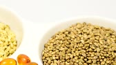 Hemp seeds, unpeeled, peeled, hemp oil capsules and hemp oil on a turn table Stok Video