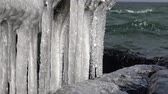 marchs financiers : Frozen water, icicles against the background of moving seawater Stock Footage