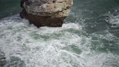 A strong storm on the sea at the precipitous shore, waves break against stones, white foam. Bulgaria