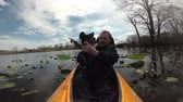 canoe : Floating on the lake kayak, the videographer takes a lake overgrown with water plants, a water lily, Canadian geese and turtles, Carnegie Lake, New Jersey