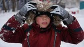 ангельский : beautiful child smiling in the winter park. Its snowing