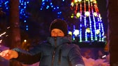 sparkler : The child holds the sparklers outdoors in the winter. Slowmotion . In the background, lights and garlands of Christmas fir