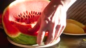 vegetable : Mens hands cut the juicy red watermelon into pieces close-up