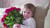 Happy baby holding a big bouquet of scarlet roses.A gift for mothers birthday