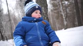 A small child walks in the winter Park. A Sunny winter day. Fun and games in the fresh air.
