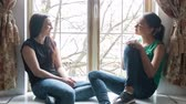 черный : slide the camera from left to right, two girls sitting on the window sill and talk. Dressed in jeans and t-shirts