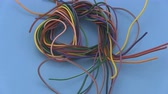 amper : Close up of multicoloured six amp electrical wire rotating on a blue background. Stok Video