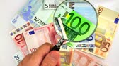 devaluation : Hand holding magnifying glass up to Euro banknoes for economists Stock Footage