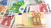 devaluation : Camera pans left to right over Euro banknotes. Camera flies over Euro money. Pan Video.  Stock Footage