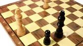 bishop : White king under attack by a black pawn. Chess game board, composition with two bishop and a pawn.  Stock Footage