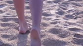 pootafdrukken : Female feet close up. Rear view, only the ankles and feet. Girl walking barefoot on sand at sunset in slow motion