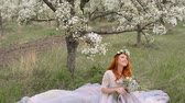 сбор винограда : Beautiful young red-haired woman dressed in a luxurious dress sits on the grass in a blooming spring garden Стоковые видеозаписи