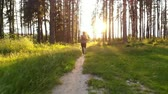 woman runs along path in forest at dawn, slow motion Stok Video