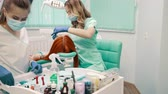 ortodôntico : woman dentist and her assistant prepare patient for dental treatment