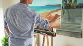 cavalete : male painter paints landscape on canvas in his art studio