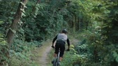 adrenaline : extreme bicyclist rides on forest path, slow motion