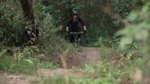 realizar : man cyclist rides off-road in forest, close-up