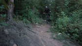 realizar : mountain biker rushes along road in forest, slow motion Stock Footage