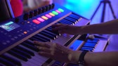concerto : keyboard player playing synthesizer during band performance, close-up