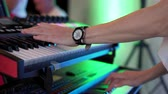 スキー : keyboard player playing synthesizer during band performance, close-up