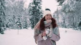 parques : happy woman walking in snow-covered park holding smartphone