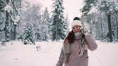 parques : young woman talking on phone in snowy park