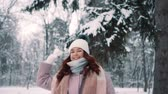 śnieżka : female throws snowballs in park, slow motion