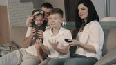 apartamentos : Young family emotionally watching football on tv Stock Footage