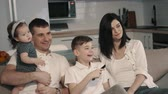 apartamentos : Happy family watching tv at home on couch Stock Footage