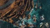 kanári szigetek : Ocean waves crash against sharp cliffs of shore, drone shot