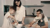 diyalog : Young happy family cooking dinner together in kitchen Stok Video