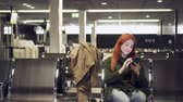 casual sitting : Young female uses phone in airport terminal