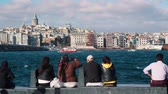 ISTANBUL, TURKEY - NOVEMBER 4, 2018: people sit on waterfront and look at Bosphorus