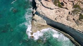falésias : Strong waves break on rocky seashore on sunny day, view from above